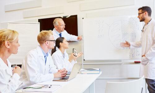 Ärzte bei einer Schulung mit Pharmareferent am Whiteboard